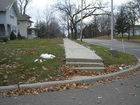Steps and a non ADA compliant curb cut in Flint, Michigan make this sidewalk impossible to use by anyone requiring a mobility device.  Photo by Barbara McCann